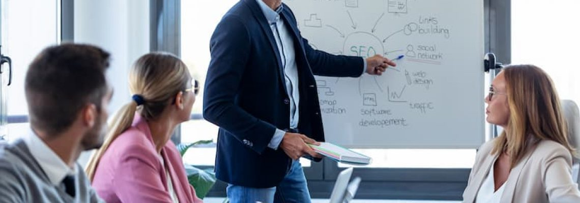 handsome-businessman-pointing-at-white-blackboard--J92ZW6D (1)